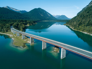 Aerial photograph of a bridge at lake Sylvenstein with mountain reflection