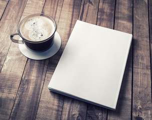 Blank closed book and coffee cup on vintage wooden background. Responsive design template.