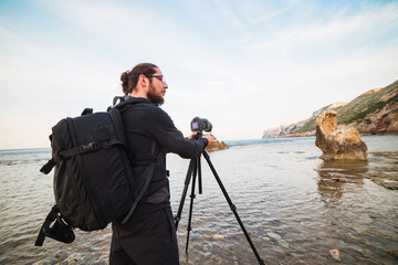 Young stylish photographer making photos of sea with the camera on a tripod