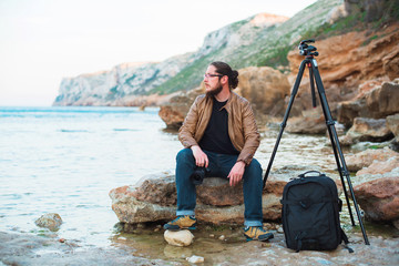 Young stylish photographer sitting on rock and looking at sea with camera in hands