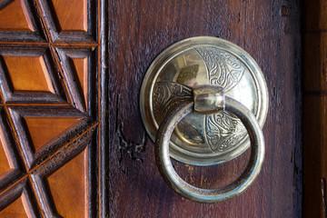 Closeup of antique copper ornate door knocker over an aged wooden door, Suleymaniye Mosque, Istanbul, Turkey