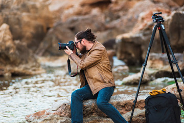 Young stylish photographer sitting on rock beach and making photo of sea