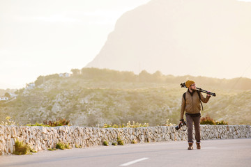 Young photographer walking on desert road with tripod on his shoulder and camera in hand