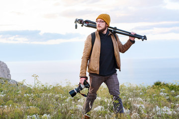Young photographer walking in the nature with tripod on his shoulder and camera in hand