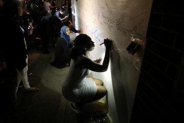 A woman writes a message of condolence on a wall  near a tower block severely damaged by a serious fire, in north Kensington, West London