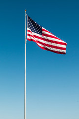 American Flag with the background of a blue sky.