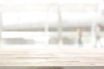 Wood table top on white blur abstract background from outdoor covered walkway in the city