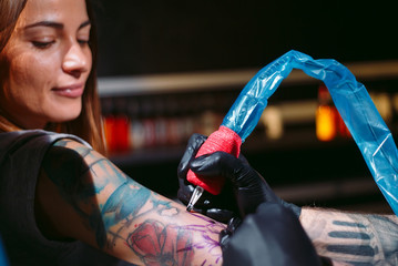 Professional tattoo artist makes a tattoo on a young girl's hand.
