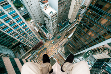 Extreme photography concept, Man sitting at the edge of a building taking photo