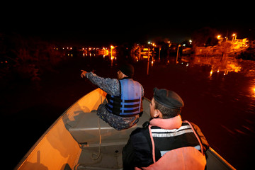 Members of the Uruguayan Prefectura (coastguard) inspect a flooded area in the Uruguayan city of Salto, on the banks of the Uruguay River