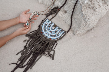 close up of woman hands holding necklace with handmade bag outdoors