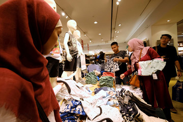 Costumers holds a cloths during late night Ramadan shopping at Gandaria Mall in Jakarta