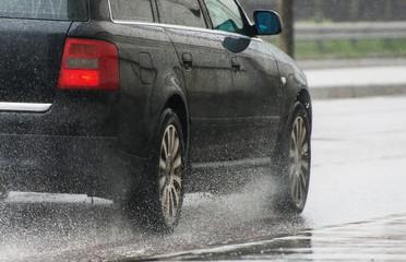 Car riding down the street in the rain.