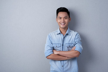 Waist-up portrait of confident Asian man posing for photography while standing against gray wall with arms crossed