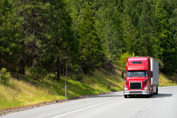 Modern red semi truck with dry van trailer driving on road with green trees forest on the roadside hills