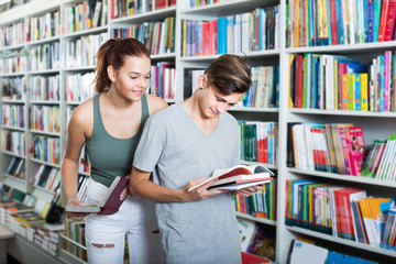 Smiling teenagers holding book and reading together