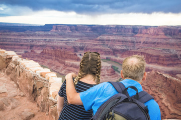 View from behind of a couple enjoying the view of the beautiful canyons of the Colorado River at Dead Horse Point State Park near Moab, Utah. Admiring the beauty of the scenic destination
