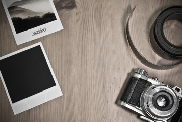 Retro vintage photography concept of two instant photo frames cards on wooden background with images of nature and text and blank black photo frame with old camera and film strip top view
