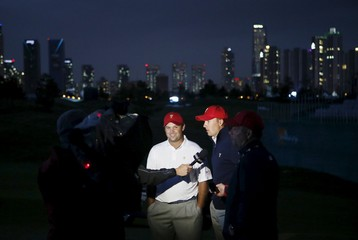 U.S. team member Reed and Spieth are interviewed after defeating international team members Day and Schwartzel on the sixteenth green during the four ball matches of the 2015 Presidents Cup golf tournament in Incheon