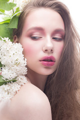 A young girl with lilac and bright creative make-up. Beautiful model with flowers and long hair. White isolated background. Pure shining skin. Beauty of the face. Spring picture.