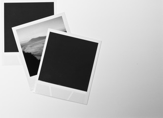 still life retro vintage three instant photo frames cards on white background with a photo of landscape in black and white with copy space text