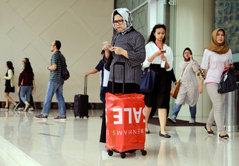 A woman holds her phone while shopping at Senayan City Mall in Jakarta