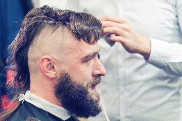 Bearded man with a mohawk in the barbershop