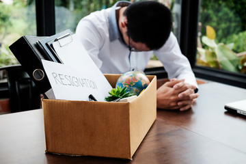 Sad dismissed businessman sitting outside the office after losing his job