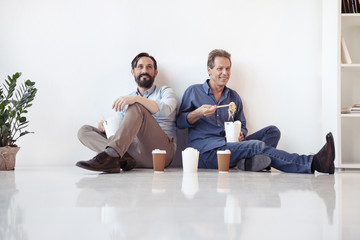 Two middle aged businessmen eating asian food and drinking coffee while sitting on floor in office