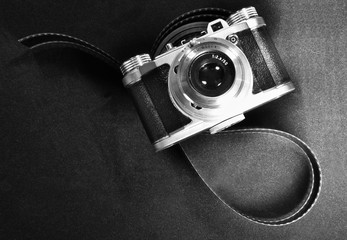 top view nostalgic art concept of old retro vintage camera and film strip in black and white