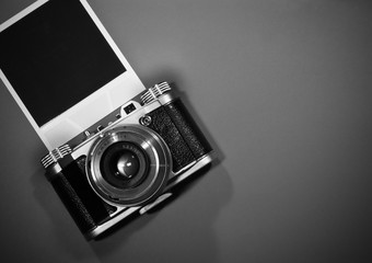 blank instant photo frame on gray background highlighted with old retro vintage camera and copy space in black and white