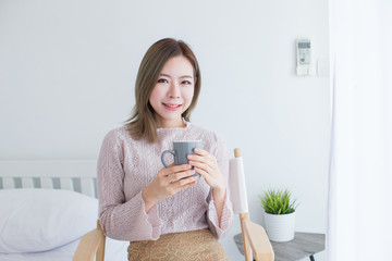 Young Asian girl drinking coffee in bedroom with copy space