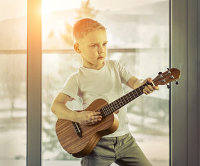 Young boy play on guitar at home at sunny day. Boy play on ukule