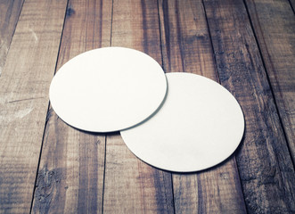 Two blank white beer coasters on vintage wooden table background. Responsive design mockup.
