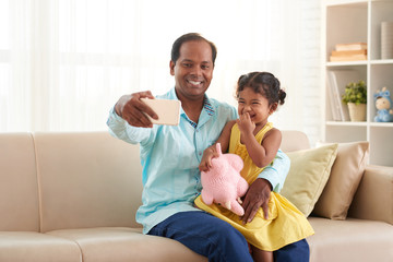 Pretty little girl with wide smile sitting on laps of her middle-aged father and posing for photography, he taking picture of themselves while sitting on cozy sofa