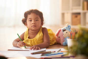 Cute little girl distracted from drawing picture with colored pencil and looking at camera seriously, blurred background