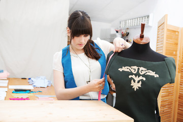 Young female fashion designer working on garment  on a mannequin at her studio.