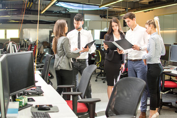 Businesspeople having a business meeting in the office. Group of young business people in formal wear are standing and discussing documents.