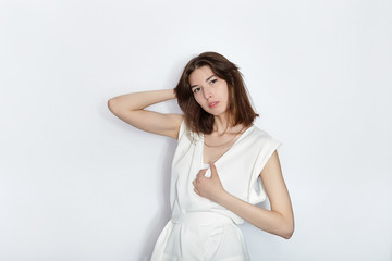 Young beautiful brunette beginner model woman in white blouse practicing posing showing emotions on white wall studio background