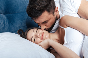 Portrait of young loving couple embrace in bed
