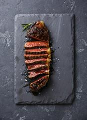 Sliced medium rare grilled Striploin steak on slate board