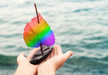 Small decorative sailboat with a rainbow a sail in LGBT colors in the hands against the background of the sea. Conceptual image of holiday, freedom