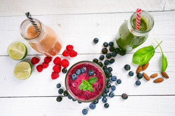 Blueberry, spinachy and orange smoothie on a wooden white background. Glasses of smoothie with berry and mint. Berry, leaf and lime, raspberries on a table. Fruit Healthy food. Breakfast.