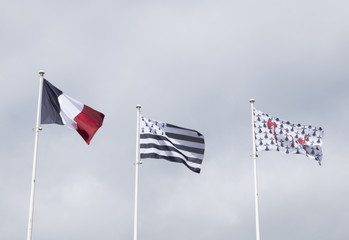 Three flags in the wind: a French flag, a Breton flag and the flag of Concarneau. In the background a very cloudy sky.