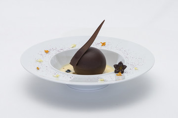 Luxurious dessert with chocolate globe and vanilla sauce, served on a biscuit, decorated with chocolate flower, flower petals and forest fruits, served in a white plate, light background, isolated
