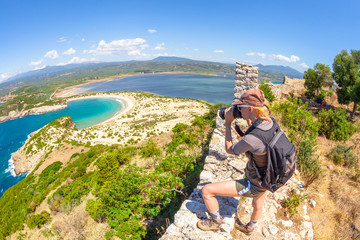 Travel woman photographer takes shot of Voidokilia Beach from famous Navarino Castle ruins in Pylos, Peloponnese, Greece after hiking.Hiker woman photographing on fortress walls. Scenic fish eye view.