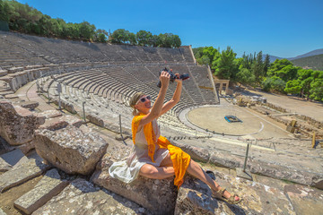 Travel female photographer takes a selfie with professional camera. Woman sitting on steps of Epidaurus theater, takes pictures in Archaeological Site, Peloponnese, Greece. Summer holidays lifestyle.