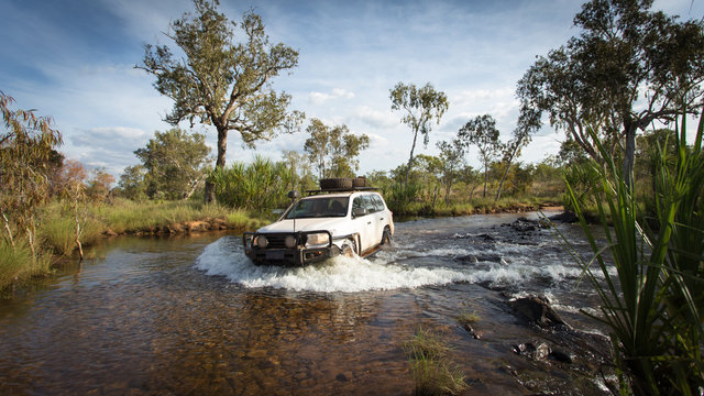 A Four wheel drive vehicle crosses a flowing creek in the far North Kimberley of Western Australia on the road to Mitchell Plateau.