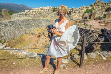 Travel photographer lifestyle. Seductive woman in flaming greek clothes checking her camera. Archaeological Site of Ancient Mycenae, Peloponnese, Greece. Female photographer in Europe Heritage Site.