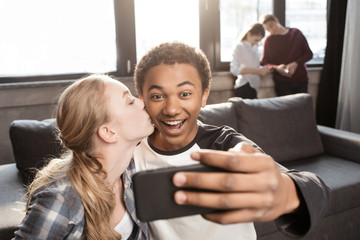 Happy teenage couple taking selfie with friends standing behind, teenagers having fun concept